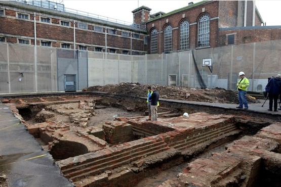 The archeological dig site inside the former Gloucester prison. The red bricks are remains of the 18th century prison building, the stone work and walls date back to 1120.  Photo by Andrew Higgins 07-12-2015